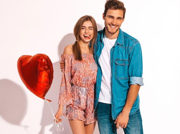Il ritratto di bella ragazza sorridente e del suo ragazzo bello che tengono il cuore hanno modellato i palloni e la risata. coppia felice in amore. buon san valentino