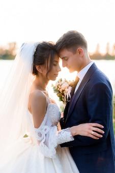 Il ritratto di bella sposa e sposo con gli occhi chiusi sta abbracciando vicino all'acqua all'aperto la sera