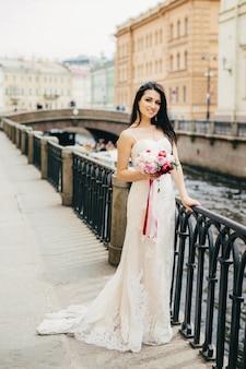 Il ritratto di bella sposa femminile attraente porta il vestito da sposa bianco lungo, tiene il mazzo