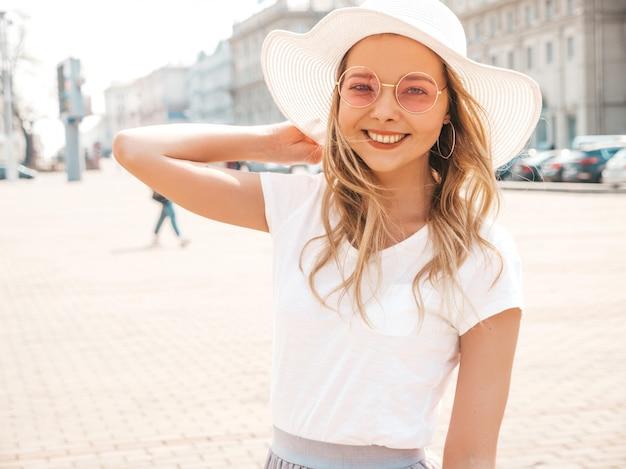 Il ritratto di bello modello biondo sorridente si è vestito in vestiti dei pantaloni a vita bassa dell'estate. ragazza d'avanguardia che posa nella via in occhiali da sole e cappello rotondi. divertimento donna divertente e positiva