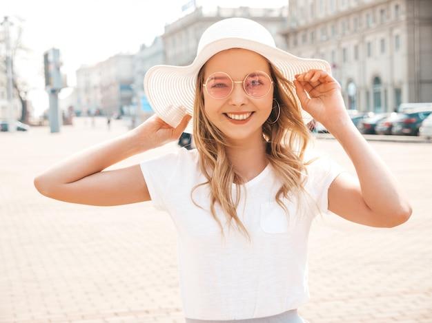 Il ritratto di bello modello biondo sorridente si è vestito in vestiti dei pantaloni a vita bassa dell'estate. ragazza d'avanguardia che propone in strada in occhiali da sole rotondi. donna divertente e positiva divertendosi in cappello
