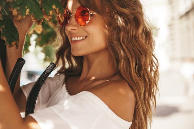 Il ritratto di bello modello biondo sveglio dell'adolescente senza trucco in vestito bianco dai pantaloni a vita bassa dell'estate copre la posa sui precedenti della via in occhiali da sole che toccano le foglie dell'albero