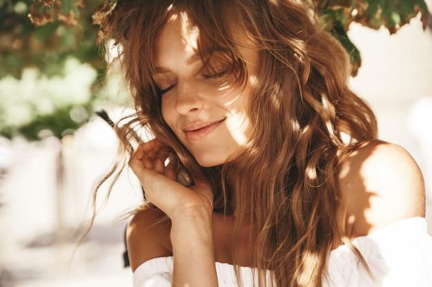 Il ritratto di bello modello biondo sveglio dell'adolescente senza trucco in vestito bianco dai pantaloni a vita bassa dell'estate copre la posa sui precedenti della via. occhiali da sole sul viso