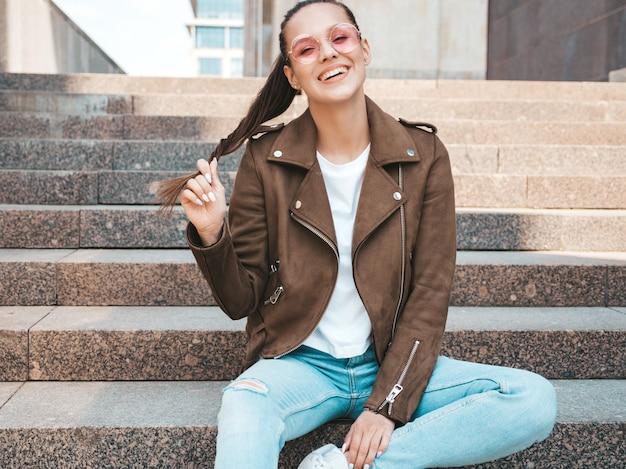 Il ritratto di bello modello castana sorridente si è vestito in vestiti del rivestimento e dei jeans dei pantaloni a vita bassa dell'estate. ragazza d'avanguardia che si siede sui gradini nei precedenti della via. donna divertente e positiva in occhiali da sole rotondi