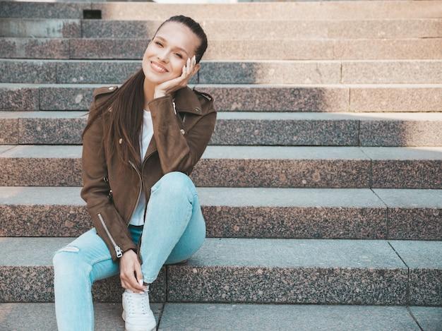 Il ritratto di bello modello castana sorridente si è vestito in vestiti del rivestimento e dei jeans dei pantaloni a vita bassa dell'estate. ragazza d'avanguardia che si siede sui gradini nei precedenti della via. donna divertente e positiva