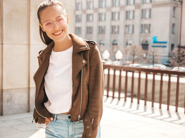 Il ritratto di bello modello castana sorridente si è vestito in vestiti della giacca dei pantaloni a vita bassa dell'estate