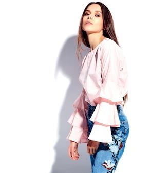 Il ritratto di bello modello sorridente caucasico della donna castana in blusa rosa luminosa e le blue jeans alla moda dell'estate con i fiori stampa