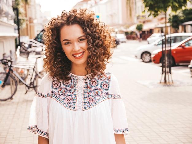 Il ritratto di bello modello sorridente con l'acconciatura dei riccioli di afro si è vestito in vestito bianco dai pantaloni a vita bassa dell'estate.