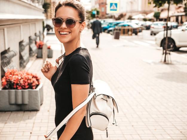 Il ritratto di bello modello sorridente si è vestito in vestiti dell'estate. ragazza d'avanguardia che posa nella via in occhiali da sole. divertimento donna divertente e positiva