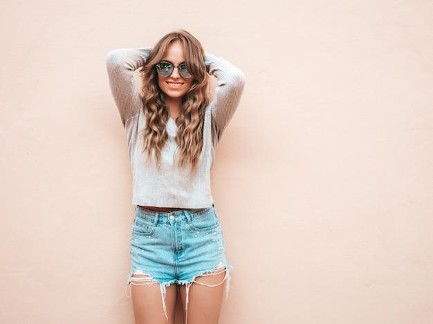 Il ritratto di bello modello sorridente si è vestito in vestiti di shorts dei jeans dei pantaloni a vita bassa dell'estate