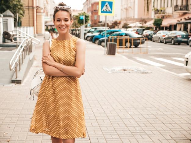 Il ritratto di bello modello sorridente si è vestito in vestito da giallo dell'estate. ragazza d'avanguardia che propone nella via. divertimento donna divertente e positiva
