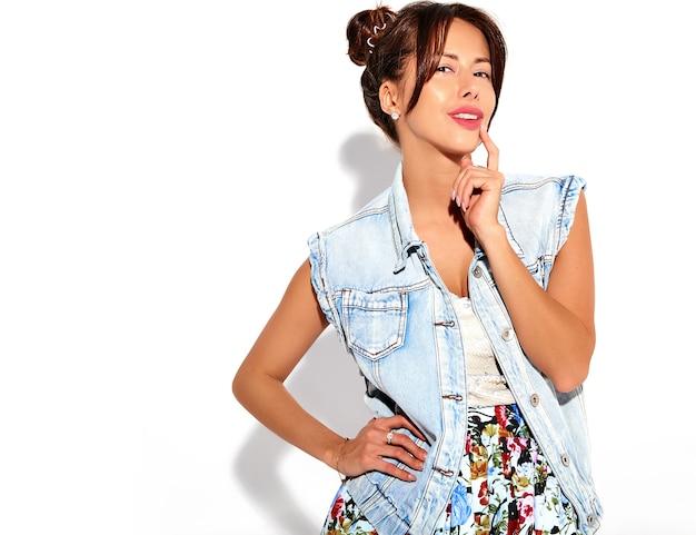 Il ritratto di bello modello sveglio della donna del brunette in jeans casuali dell'estate copre senza trucco con l'acconciatura dei corni isolata su bianco