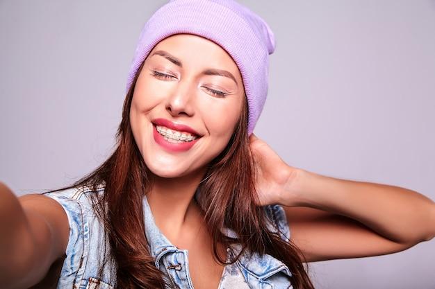 Il ritratto di bello modello sveglio sorridente della donna castana in jeans casuali dell'estate copre senza trucco in berretto porpora che fa la foto del selfie sul telefono isolato su gray