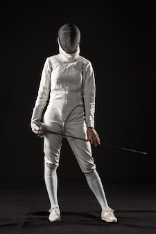 Il ritratto di donna che indossa un costume da scherma bianco su fondo nero