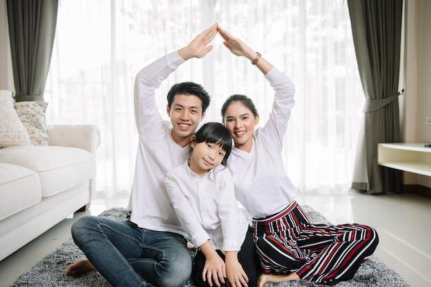 Il ritratto di famiglia asiatico con la gente felice che sorride esamina la macchina fotografica nella casa.