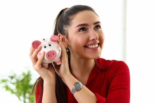 Il ritratto di giovane bella donna castana sorridente in camicia rossa che tiene la scatola rosa di porcellino per soldi dentro consegna il fondo bianco in ufficio. signora alla moda di affari, segretaria, la gente nel concetto dell'ufficio