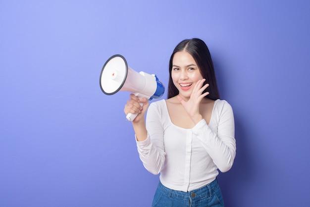 Il ritratto di giovane bella donna sorridente sta usando il megafono per annunciare sopra la porpora isolata