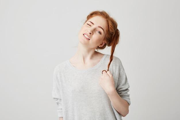 Il ritratto di giovane bella ragazza della testarossa scioglie i capelli commoventi del panino.