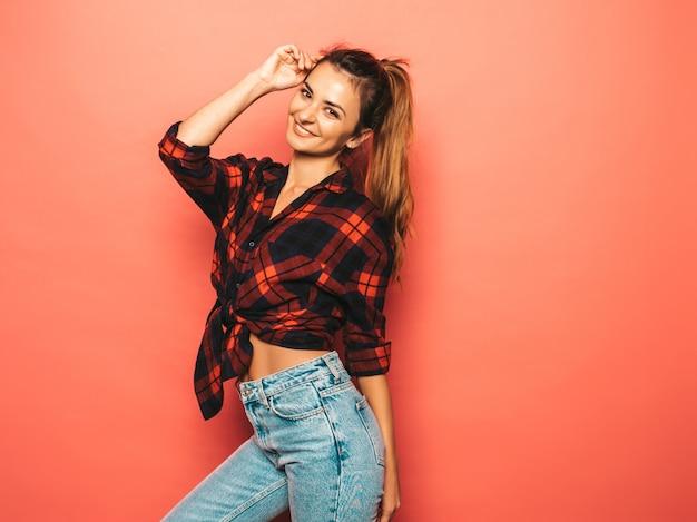 Il ritratto di giovane bella ragazza sorridente dei pantaloni a vita bassa in camicia a quadretti dell'estate d'avanguardia e vestiti dei jeans. donna spensierata sexy che posa vicino alla parete rosa in studio. modello positivo senza trucco