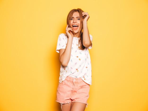 Il ritratto di giovane bella ragazza sorridente dei pantaloni a vita bassa negli shorts d'avanguardia dei jeans dell'estate copre. donna spensierata sexy che posa vicino alla parete gialla. divertimento del modello positivo