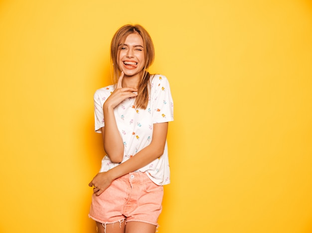 Il ritratto di giovane bella ragazza sorridente dei pantaloni a vita bassa negli shorts d'avanguardia dei jeans dell'estate copre. donna spensierata sexy che posa vicino alla parete gialla. modello positivo divertendosi e mostrando lingua