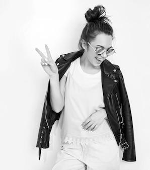 Il ritratto di giovane bello modello della ragazza della donna castana con il rivestimento nudo che indossa il rivestimento di cuoio del motociclista dei pantaloni a vita bassa dell'estate copre in occhiali da sole che posano vicino alla parete. mostrando la sua lingua e il segno di pace