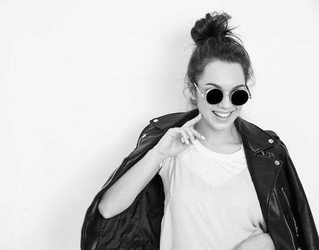 Il ritratto di giovane bello modello della ragazza della donna castana con il rivestimento nudo che indossa il rivestimento di cuoio del motociclista dei pantaloni a vita bassa dell'estate copre in occhiali da sole che posano vicino alla parete.
