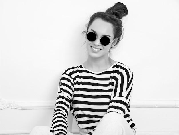 Il ritratto di giovane bello modello della ragazza della donna castana con trucco nudo in pantaloni a vita bassa dell'estate copre la posa vicino alla parete in occhiali da sole. sedendo sul pavimento