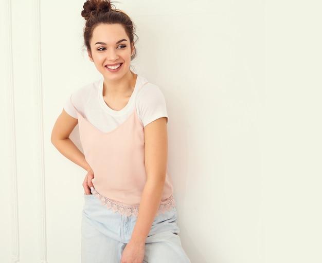 Il ritratto di giovane bello modello della ragazza della donna castana con trucco nudo in pantaloni a vita bassa variopinti di rosa dell'estate copre la posa vicino alla parete. guardando felicemente