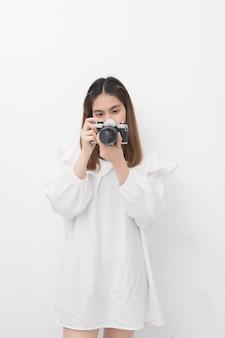 Il ritratto di giovane donna asiatica che tiene la macchina fotografica d'annata per prende una foto, fotografo della donna nell'azione su fondo bianco.