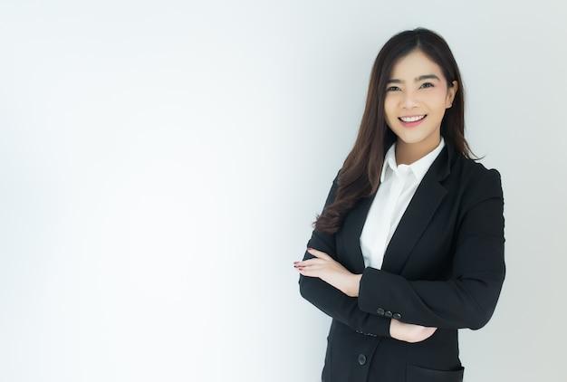 Il ritratto di giovane donna asiatica di affari ha attraversato le sue braccia sopra fondo bianco.