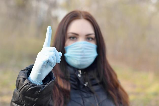 Il ritratto di giovane donna castana in maschera protettiva blu e guanti di gomma mostra il gesto di attenzione