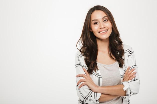 Il ritratto di giovane donna con il sorriso magnifico che sta con le armi ha piegato isolato, sopra bianco