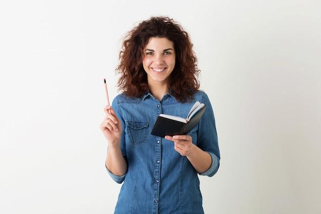Il ritratto di giovane donna graziosa sorridente naturale con l'acconciatura riccia in camicia del denim che posa con il taccuino e la penna ha isolato, l'apprendimento dello studente, avendo idea
