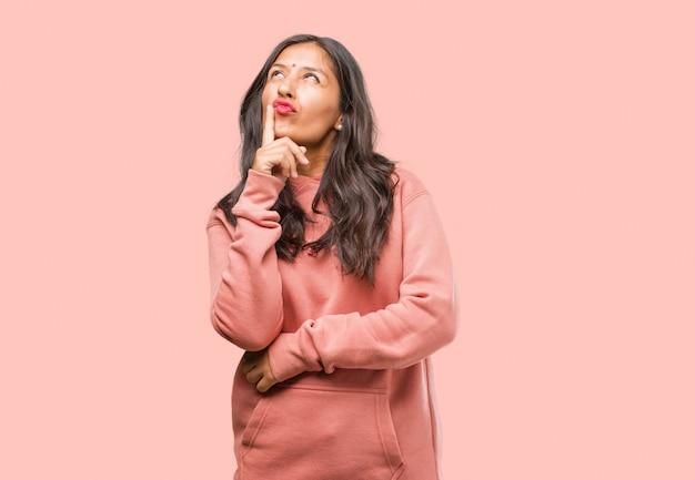 Il ritratto di giovane donna indiana di forma fisica che pensa e che cerca, confuso su un'idea, sta provando a trovare una soluzione