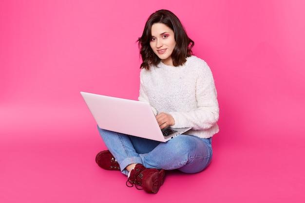 Il ritratto di giovane donna si siede con le gambe attraversate