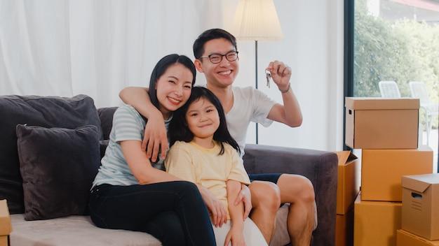 Il ritratto di giovane famiglia asiatica felice ha comprato la nuova casa. la piccola figlia prescolare giapponese con i genitori madre e padre tiene le chiavi disponibili che si siedono sul sofà in salone che sorride esaminando la macchina fotografica.