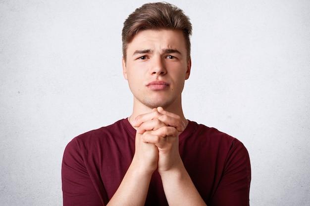 Il ritratto di giovane maschio europeo attraente tiene le palme premute