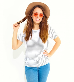 Il ritratto di giovane modello di risata alla moda della donna in estate casuale copre in cappello marrone con trucco naturale isolato sulla parete bianca