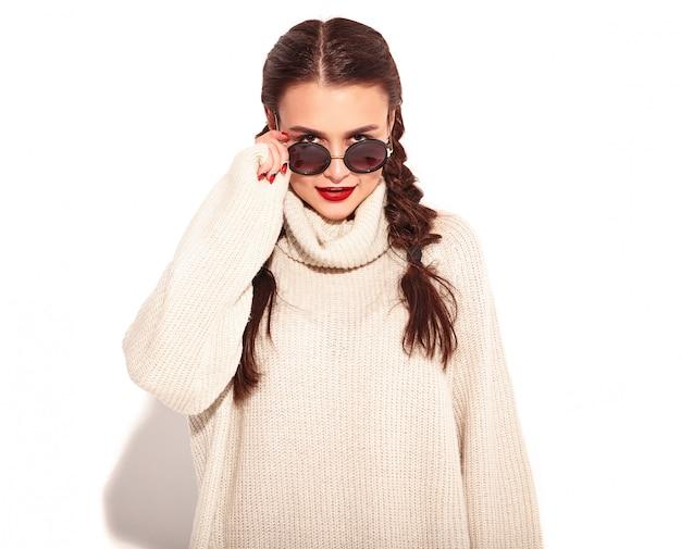 Il ritratto di giovane modello sorridente felice della donna con trucco luminoso e le labbra rosse con due trecce in estate scalda i vestiti del maglione isolati. dietro gli occhiali da sole alla moda