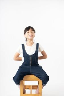 Il ritratto di giovane ragazza asiatica nasconde qualcosa dentro, isolato su fondo bianco