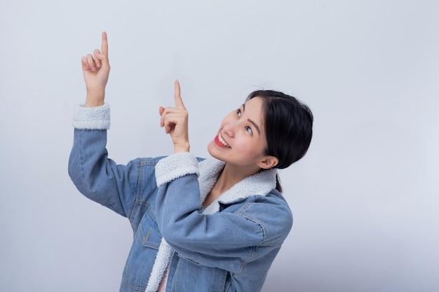 Il ritratto di giovane signora asiatica felice che indica sul fondo bianco dello spazio della copia per il prodotto, l'affare e fa pubblicità al concetto