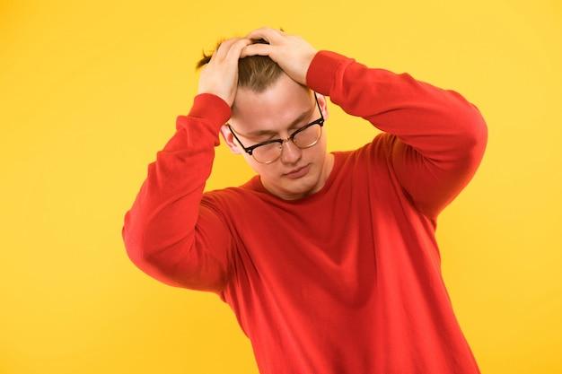 Il ritratto di giovane tipo deludente bello in maglione rosso afferra la sua testa su k giallo