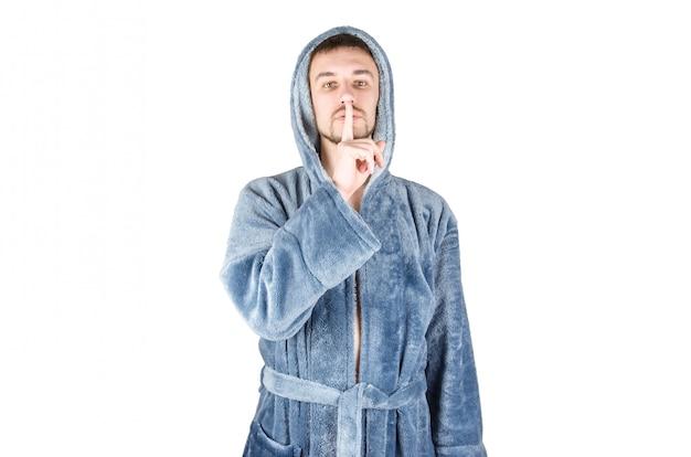 Il ritratto di giovane uomo barbuto caucasico in accappatoio blu chiede il silenzio isolato su fondo bianco
