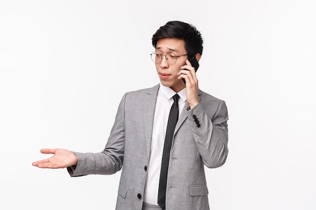 Il ritratto di giovane uomo d'affari asiatico scettico dall'aspetto serio dà la consultazione sul telefono, avendo chiamata importante dal cliente, parlando su smartphone, gesticolando mano e smorfia indeciso