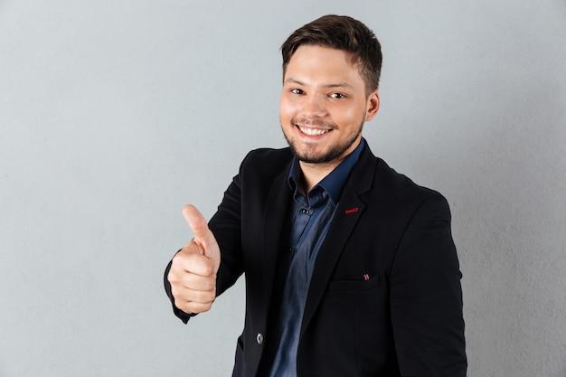 Il ritratto di giovane uomo d'affari che mostra i pollici aumenta il gesto