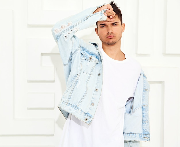 Il ritratto di giovane uomo di modello bello si è vestito in vestiti dei jeans che posano vicino alla parete strutturata bianca