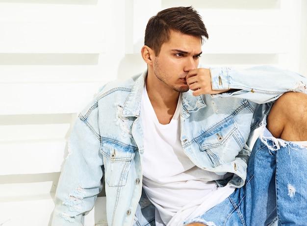 Il ritratto di giovane uomo di modello bello si è vestito in vestiti dei jeans che si siedono vicino alla parete strutturata bianca