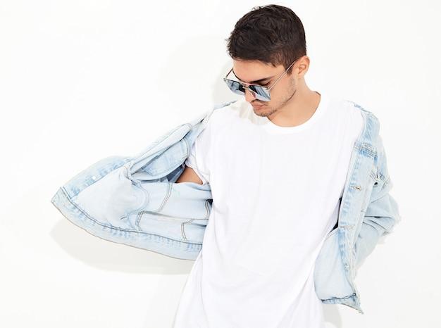 Il ritratto di giovane uomo di modello bello si è vestito in vestiti dei jeans nella posa degli occhiali da sole. isolato