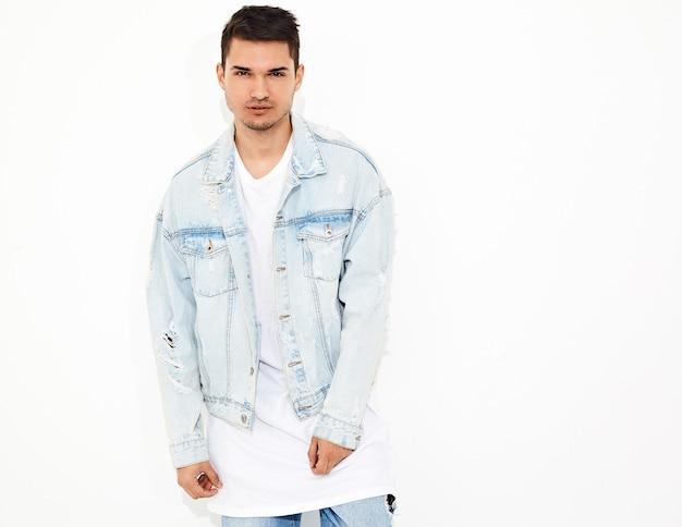 Il ritratto di giovane uomo di modello bello si è vestito nella posa dei vestiti dei jeans. isolato